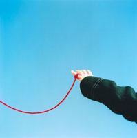 赤い糸を小指にかける男性の手
