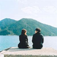水辺に座るカップルの後姿