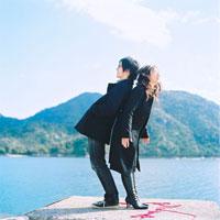 水辺で背中合わせに立つカップル