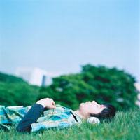 草原で音楽を聴いて寝転ぶ男性