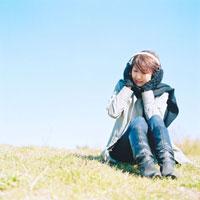 草原で音楽を聴く女性