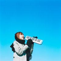 ピアニカを演奏する女性と青空