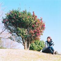 ピアニカを持って座る女性と木