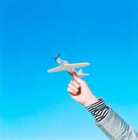飛行機を飛ばす女性の手と青空