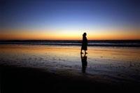 朝焼けの海を歩く女性