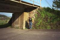 鉄橋の下に立つ女性