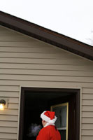 家のドアの前に立つサンタ