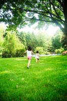 芝生の上を走る姉妹