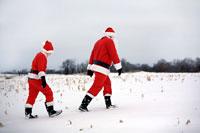 雪原を歩く大人のサンタと子供のサンタ