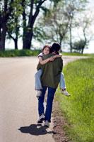 女の子を抱っこして道を歩く男の子