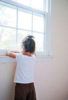 窓越しに外を眺める少女の後ろ姿