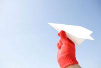 空に向かって紙飛行機を飛ばす手