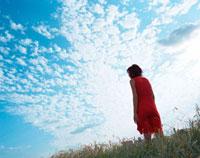 土手に立つ女性と青空 20021005709| 写真素材・ストックフォト・画像・イラスト素材|アマナイメージズ
