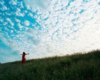 土手に立つ女性と青空 20021005710| 写真素材・ストックフォト・画像・イラスト素材|アマナイメージズ