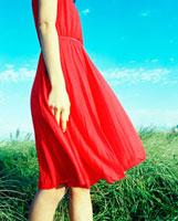 草原に立つ赤いワンピースを着た女性 20021005711A| 写真素材・ストックフォト・画像・イラスト素材|アマナイメージズ