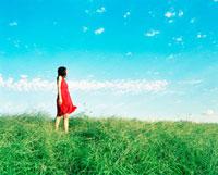 草原に立つ赤いワンピースを着た女性 20021005712| 写真素材・ストックフォト・画像・イラスト素材|アマナイメージズ