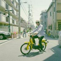 住宅街で黄色いバイクにまたがる若者