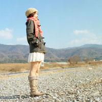 河原に立つマフラーを巻いた女性