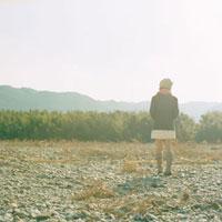 河原を歩くマフラーを巻いた女性 20021005807| 写真素材・ストックフォト・画像・イラスト素材|アマナイメージズ