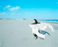 ストールを広げて走る女性と砂浜
