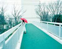 陸橋の上で赤い傘をさした女性 20021005848| 写真素材・ストックフォト・画像・イラスト素材|アマナイメージズ