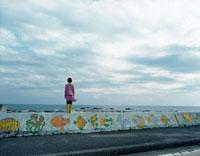海沿いの土手に立つ女の子と道