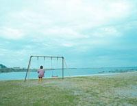 海とブランコに乗る女の子 20021005952| 写真素材・ストックフォト・画像・イラスト素材|アマナイメージズ