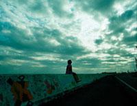 海沿いの土手に座る女の子と道