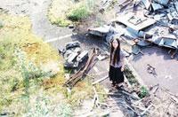 廃棄物の中に立つ女性