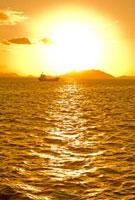 海に浮かぶ船と夕日 20021006062| 写真素材・ストックフォト・画像・イラスト素材|アマナイメージズ