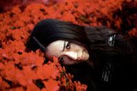 赤い花の中に顔を埋める女性