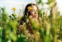 菜の花畑にうずくまる女性