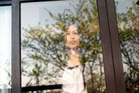 窓越しに立つ女性