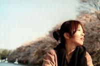 桜の咲く池ボートに乗る女性