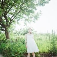 緑の中に立つ白いワンピースの女性