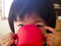 赤いコップで飲む女の子供