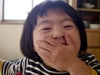 口に手をあてて笑う女の子供