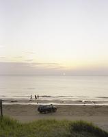夕暮れの海と波打ち際で遊ぶ若者たち 20021007181| 写真素材・ストックフォト・画像・イラスト素材|アマナイメージズ