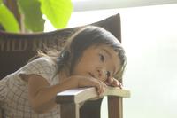 椅子にもたれ掛かっている女の子 20021007221| 写真素材・ストックフォト・画像・イラスト素材|アマナイメージズ