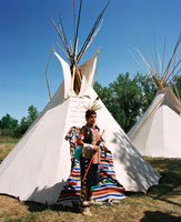 Crow teenager in front of his  tepee