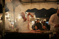Man cooking sausages on barbecue at night market