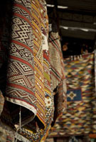 Carpets and rugs hanging up in stall in souk
