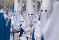 People wearing robes and masks with hoods