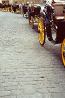 Row of horse and carriages on brick road