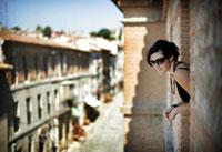 Young woman looking out of balcony window in Parador Hotel