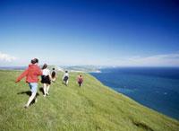 Tourists walking along ridge above coast near Lulworth Cove
