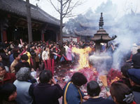 People throwing incense into fire