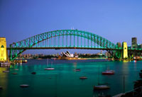 Sydney Harbour Bridge at dusk with Opera House behind