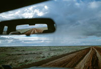 Dirt road reflected in rear view mirror