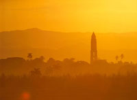 Tower silhouetted amongst orange mountains